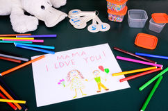 Child's drawing Mama, I love you. And a lot of colored pencils, markers and toy on the green table Stock Images