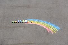 Child's drawing of rainbow and chalks on a street Stock Photo