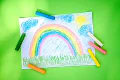 A child`s drawing of a rainbow colored crayons