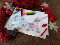 Child's drawing of Santa Claus with a bag of gifts. Celebratory tinsel and pencils around the picture Royalty Free Stock Photos
