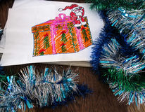 Child`s drawing of Santa Claus with a gift. Holiday decorations around the drawing Stock Image