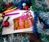 Child's drawing of Santa Claus with a gift. Holiday decorations and markers around the drawing Stock Photo