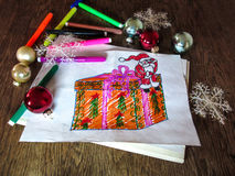 Child's drawing of Santa Claus with a gift. Holiday decorations and markers around the drawing Stock Image
