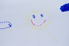 Child`s drawing of a smiling sun. On a white papper stock photo