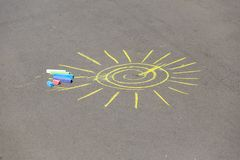 Child's drawing of sun and chalks on a street Royalty Free Stock Images