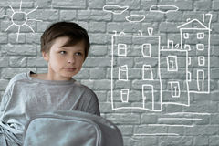 Child's drawing. Teenage boy with a road backpack sitting on brick wall background. Royalty Free Stock Images