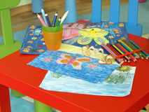 Child's drawings. Child's paintings and colorful crayons on red table stock image
