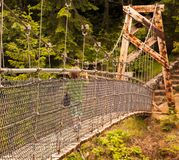 A child's exploration. A young blond  boy crosses over a suspension bridge in Mt St Helen's  National Park Stock Images