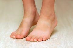 Child& x27; s-Füße auf hölzerner Beschaffenheit des Parkettlaminats breiten Nahaufnahme aus lizenzfreies stockbild