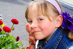 The child's face near the flowers. Royalty Free Stock Photo