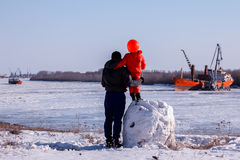 The child`s father stands on the banks of the river. Stock Photography