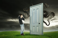 Child's fear. Young boy fearing a monster behind a door Stock Images