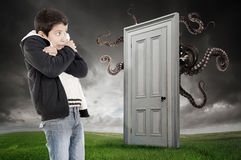 Child's fear. Young boy fearing a monster behind a door Stock Image
