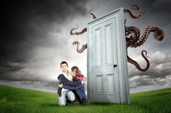 Child's fear. Young boy and girl fearing a monster behind a door Royalty Free Stock Photo
