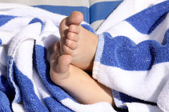 Child's feet. Crossed footed resting on a white and blue striped towel showing rough and peeling skin on the sole of the foot Royalty Free Stock Photo