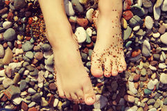 Child's feet on a beach in small color pebble in a summer sunny day. Royalty Free Stock Images
