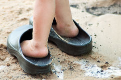 Child's feet in big sandals. On wet sand Royalty Free Stock Image