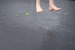 Child`s feet. Jumped over the wet asphalt Royalty Free Stock Image