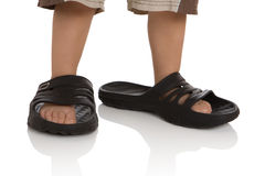Child's feet in large slippers. Child's feet in large black slippers Royalty Free Stock Image