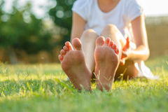 Child's feet. Little girls sitting on the grass.Feet close up. Blurred background Stock Photography