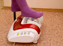 The child's feet on a roller masseur. Office of hardware massage Stock Images