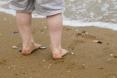 Child's feet by the shoreline Stock Images