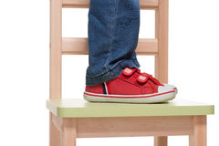Child's feet standing on the little chair Stock Photo