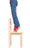 Child's feet standing on the little chair on tiptoes Stock Photos