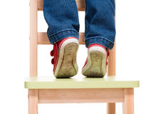 Child's feet standing on the little chair on tiptoes. On white background Royalty Free Stock Photos