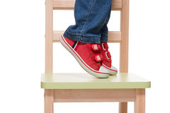 Child's feet standing on the little chair on tiptoes. On white background Stock Photos