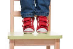 Child's feet standing on the little chair on tiptoes. On white background Royalty Free Stock Photo