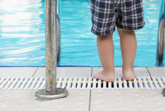 Child's feet standing by a swimming pool Stock Photo