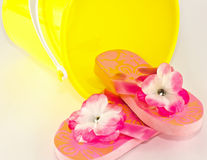 Child's Flip Flops and Sand Toy. Little girl's pink flower flip flops and bright yellow sand bucket toy stock photos