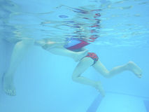 The child`s foot and adult under water in the pool. Underwater photography Stock Images