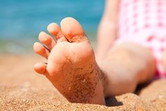 Child's foot is close to the sandy beach Royalty Free Stock Image