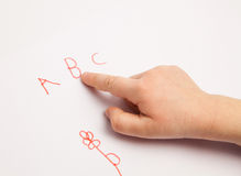 Child's forefinger indicating on letters. White background stock photos