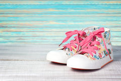 Child's girl kid's textile lace shoes pair wooden background. Royalty Free Stock Photo
