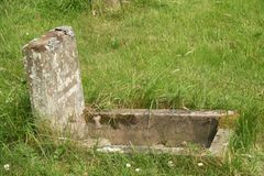 Child's grave. Very old child's gravestone where the inscription has been erroded with time stock image