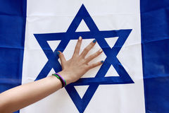Child`s hand on the background of the Israeli flag Stock Photos