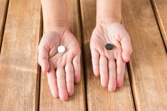The child`s hand with black and white pills on wooden background stock images
