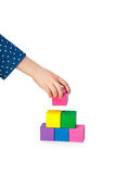 Child's hand building a brick tower isolated on white Royalty Free Stock Photos