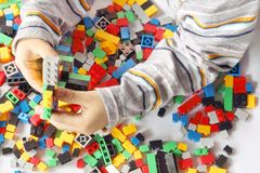 Child`s hand building plastic toy blocks with blurred background.  stock photos