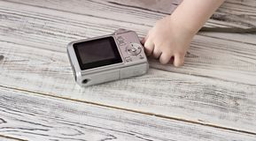 Child`s hand and camera, close-up, wooden background photography stock image