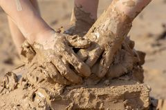 Child`s hand in clay mud mixing around outside on a sunny day making a mess stock photography