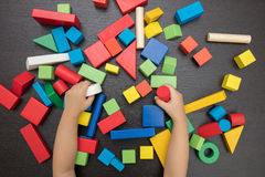 Child`s hand close up playing building blocks Stock Photography