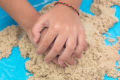 Child`s hand close up playing kinetic sand Royalty Free Stock Images