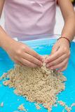 Child`s hand close up playing kinetic sand Stock Image