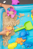 Child`s hand close up playing kinetic sand Royalty Free Stock Photos