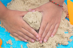 Child`s hand close up playing kinetic sand Royalty Free Stock Image