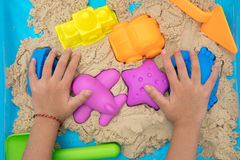Child`s hand close up playing kinetic sand Stock Images